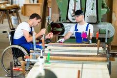 轮椅的工作者在有他的colleagu的木匠的车间 库存图片