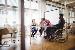 轮椅的工友有照片编辑程序的在会议室 图库摄影