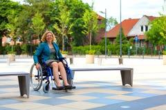 轮椅的年轻妇女在街道上 免版税库存照片