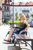 轮椅的年轻妇女在街道上 免版税库存图片
