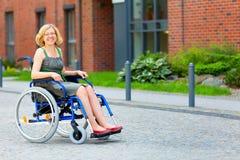 轮椅的年轻妇女在街道上 免版税图库摄影