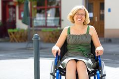 轮椅的年轻妇女在街道上 库存照片