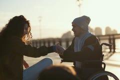 轮椅的年轻残疾人提出一个提案给他的女朋友在阳光 免版税库存照片