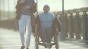 轮椅的年轻残疾人走与码头和谈的少妇的 股票视频