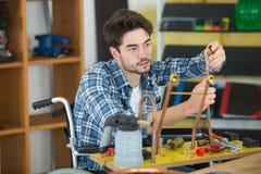 轮椅的年轻水管工工作者与铜管子一起使用 库存图片