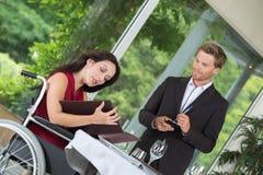 轮椅的微笑的妇女吃午餐在餐馆 库存图片