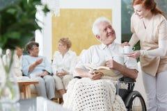 轮椅的微笑的更老的人 库存图片