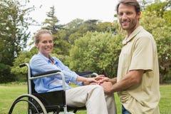 轮椅的愉快的妇女有下跪在她旁边的伙伴的 免版税库存照片