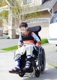 轮椅的愉快的矮小的残疾男孩 库存图片