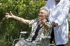 轮椅的愉快的年长妇女有开放胳膊的 免版税图库摄影