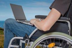 轮椅的有残障的残疾人与外面膝上型计算机一起使用 免版税库存照片