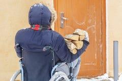 轮椅的残疾人在与木柴日志的门附近 免版税库存照片