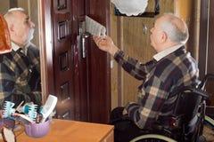轮椅的残疾人收集他的纸的 库存图片
