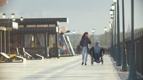 轮椅的残疾人谈话在电话一起走她的码头的女朋友 股票视频