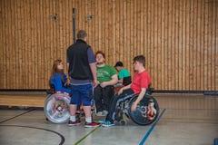 轮椅的残疾少年在体育馆里炫耀 免版税库存图片