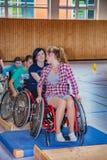 轮椅的残疾少年在体育馆里炫耀 免版税库存照片