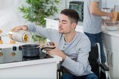 轮椅的残疾年轻人烹调膳食的在厨房里 免版税库存照片