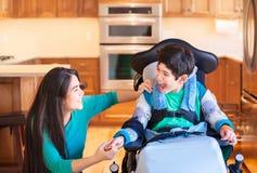 轮椅的残疾男孩笑与青少年的姐妹的在厨房里 库存照片