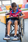 轮椅的残疾男小学生使用数字式片剂在图书馆里 库存照片