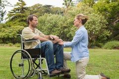轮椅的美满的人有下跪在他旁边的伙伴的 免版税库存图片