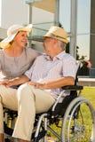 轮椅的老人微笑在他的妻子的 免版税库存图片