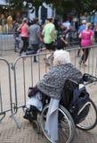 轮椅的老妇人看在连续比赛的赛跑者在荷兰城市格罗宁根街道上  免版税图库摄影