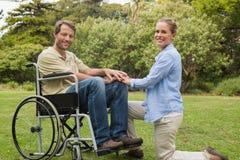 轮椅的英俊的人有下跪在他旁边的伙伴的 库存照片