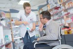 轮椅的药剂师咨询的人在药房 库存图片