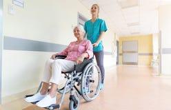轮椅的资深妇女有护士的在医院 图库摄影