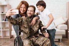 轮椅的退伍军人从军队回来了 制服的一个人在有他的家庭的一个轮椅 免版税库存图片