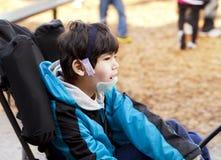 轮椅的逗人喜爱的六岁的残疾男孩在操场 免版税图库摄影