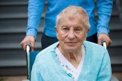 轮椅的高级夫人与看守者 免版税库存照片