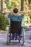 轮椅的年轻人享用新鲜空气的在一个晴天 免版税库存照片