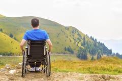 轮椅的年轻人享用新鲜空气的在一个晴天 库存照片