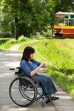 轮椅等待的电车的女孩 免版税库存照片