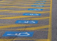 轮椅象,残疾人的国际标志,绘在蓝色和白色在一个后备的停车位的沥青 库存图片
