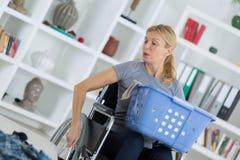 轮椅运载的篮子洗衣店的妇女在家附近 库存照片
