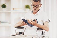 轮椅阅读书的老人在家 库存照片