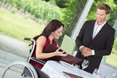 轮椅预定的膳食的妇女在餐馆 库存图片