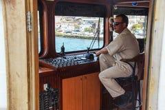 轮渡上尉等待在小船的控制 库存图片