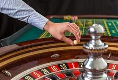 轮盘赌的赌轮和副主持人手有白色球的在赌博娱乐场 免版税库存图片