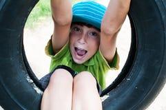 轮胎摇摆的男孩 免版税库存照片