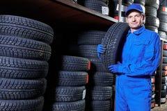 轮胎替换 技工藏品冬天轮胎在商店仓库里 库存图片
