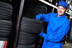 轮胎替换 拿着轮胎的技工在商店仓库里 免版税库存照片