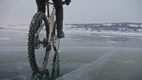 轮胎看法  射击180fps 人在冰骑自行车 在照相机前面的骑自行车者裁减 冰片断 股票视频