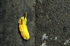 轮胎踩的印象在放置在街道天沟的香蕉的 库存照片