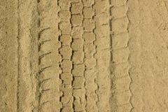 轮胎踪影在沙子的 背景理想的沙子纹理 免版税库存照片