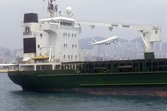 货轮船在香港港口和在起飞的喷气式客机 免版税库存照片