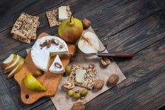 软制乳酪乳酪用核桃、蜂蜜和梨在土气桌上 玻璃白葡萄酒 顶视图 图库摄影
