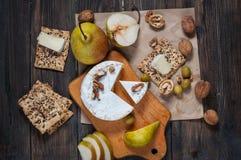 软制乳酪乳酪用核桃、蜂蜜和梨在土气桌上 玻璃白葡萄酒 顶视图 库存照片
